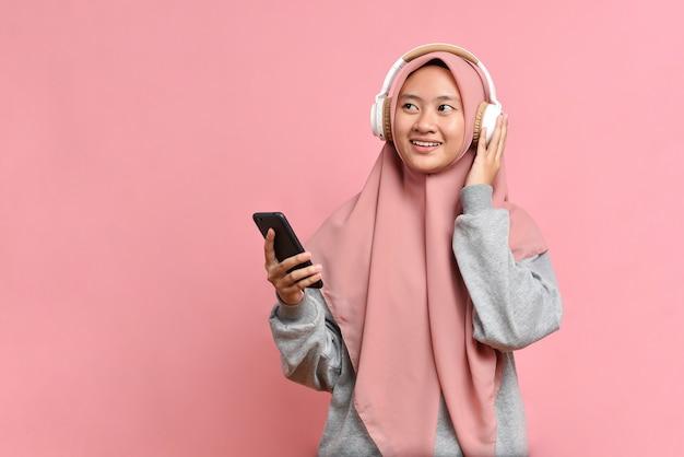 Une femme musulmane heureuse et énergique danse joyeusement, apprécie la musique préférée, porte des écouteurs stéréo, regarde l'espace de copie, isolée sur fond rose, exprime une humeur positive