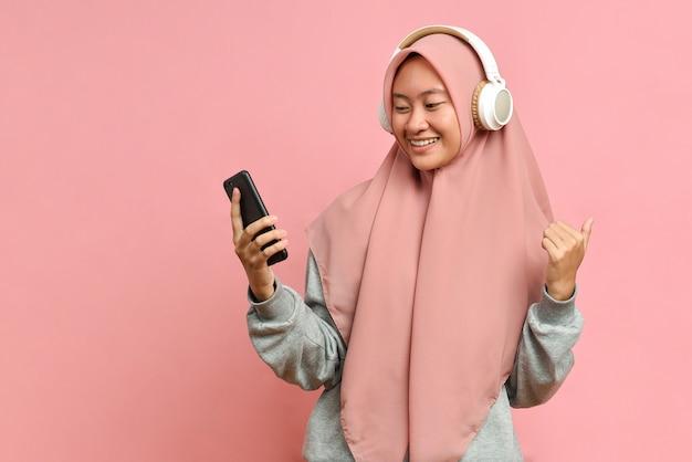 Une femme musulmane heureuse et énergique danse joyeusement, apprécie sa musique préférée, porte des écouteurs stéréo, isolée sur fond rose, exprime une humeur positive