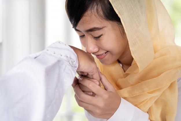 Femme musulmane avec hijab embrassant la main
