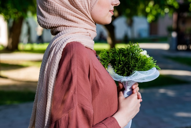 Femme musulmane en hijab tenant des fleurs