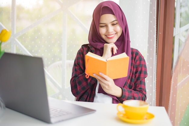 Femme musulmane avec hijab travaille avec un ordinateur portable dans un café
