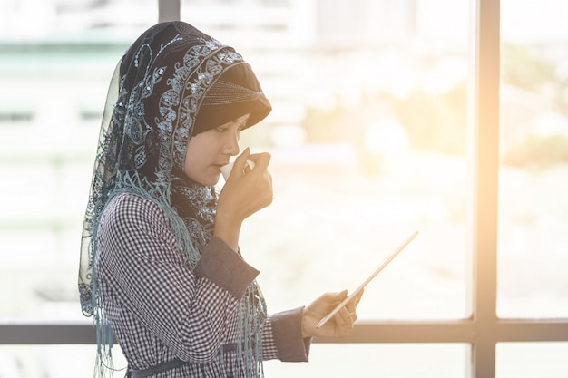 Femme musulmane islamique boit du café en regardant une tablette