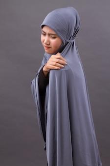 Femme musulmane islamique avec douleur à l'épaule ou au cou, raideur, blessure
