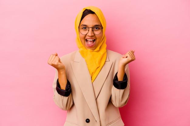 Femme musulmane jeune entreprise isolée sur mur rose applaudissant insouciant et excité. concept de victoire.