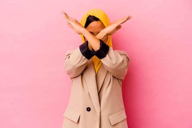 Femme musulmane jeune entreprise isolée sur un mur rose en gardant deux bras croisés, concept de déni.
