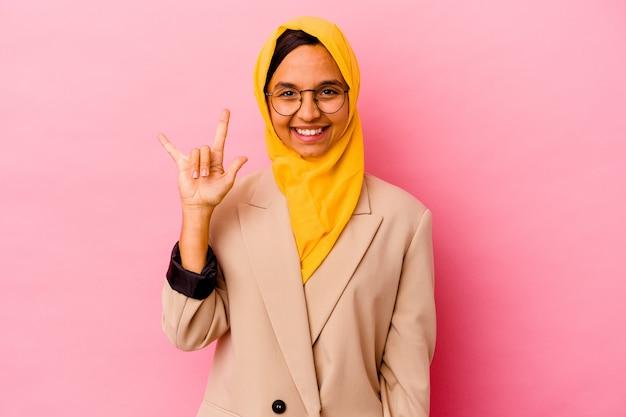 Femme musulmane jeune entreprise isolée sur un mur rose montrant un geste de cornes comme un concept de révolution.