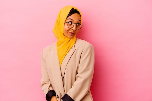 Femme musulmane jeune entreprise isolée sur un mur rose regarde de côté souriant, gai et agréable.