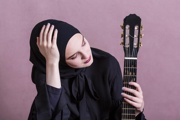 Femme musulmane jouant de la guitare