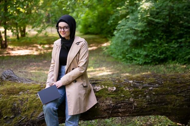 Femme musulmane lisant un livre dans le parc pendant son temps libre
