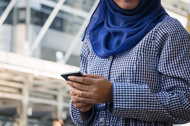 Femme musulmane, messagerie sur un téléphone portable dans la ville