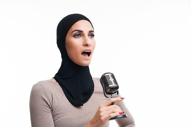 Femme musulmane avec microphone over white