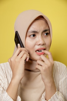 Femme musulmane portant le hijab avec une expression triste de téléphone appelant isolé sur fond jaune