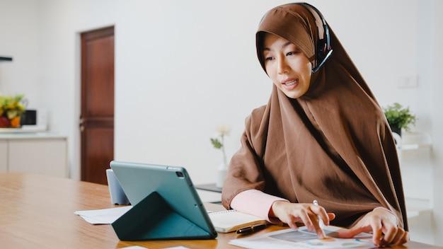 Une femme musulmane porte un casque à l'aide d'une tablette numérique parle à ses collègues du rapport de vente lors d'une conférence vidéo tout en travaillant à domicile dans la cuisine.