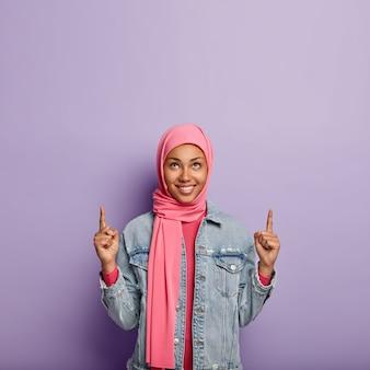 Une femme musulmane positive pointe en haut, discute d'un événement intéressant et heureux qui se déroule vers le haut