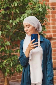Femme musulmane prenant selfie heureuse belle fille avec écharpe prendre une photo d'elle-même à l'aide d'un smartphone