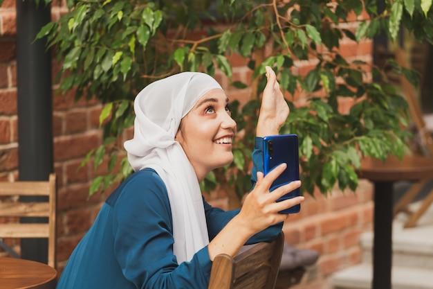 Femme musulmane prenant selfie. heureuse belle fille avec écharpe prendre une photo d'elle-même à l'aide d'un smartphone.