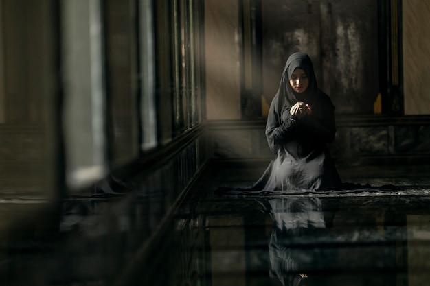 Femme musulmane en prière dans la mosquée