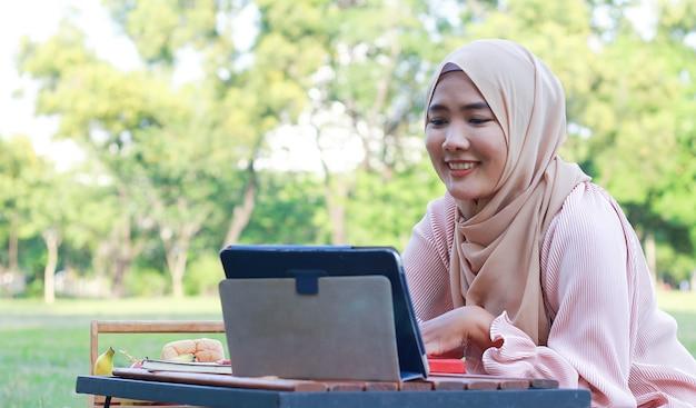 Femme musulmane se détendre et travailler dans le parc en vacances