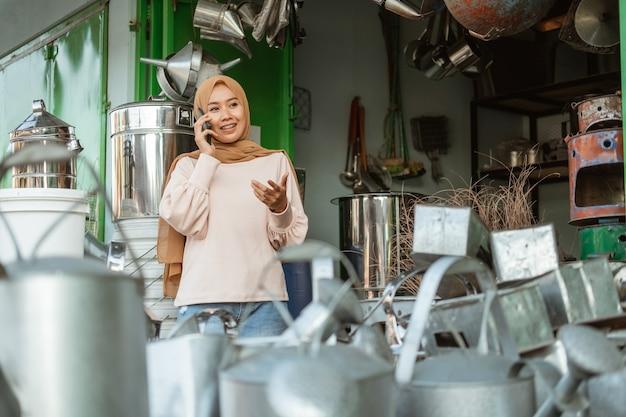 Femme musulmane se tient à l'aide de handphones dans le magasin d'appareils ménagers