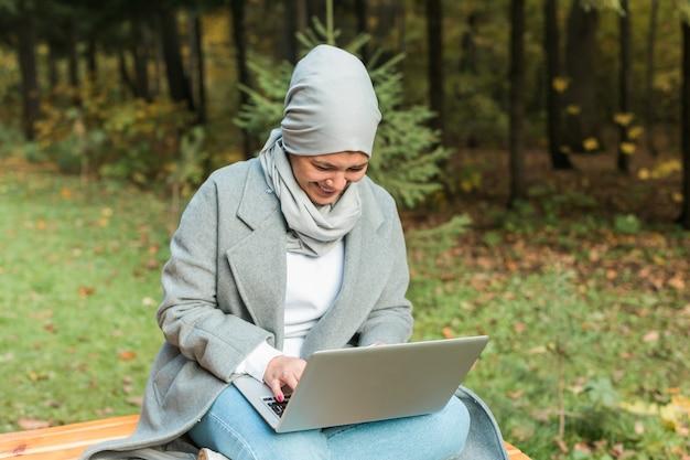 Femme musulmane avec son ordinateur portable dans le parc