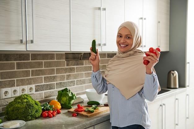 Une femme musulmane souriante en hijab montre un concombre et des tomates à la caméra tout en préparant une salade végétalienne dans la cuisine.