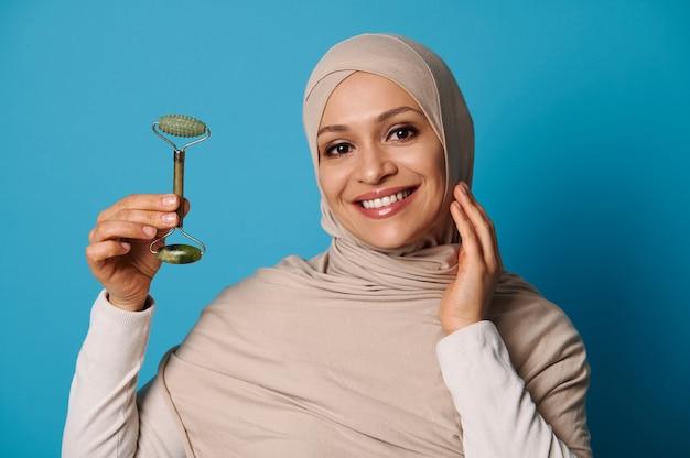 Femme musulmane souriante portant un hijab beige tenant un masseur à rouleaux de jade, posant en regardant la caméra