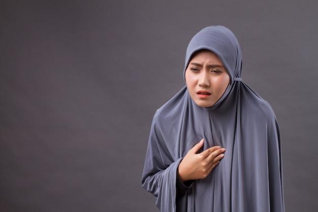 Femme musulmane stressée malade avec reflux acide, symptômes de gerd