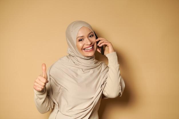 Femme musulmane avec tête couverte en foulard sourit à l'avant avec un sourire à pleines dents et montre un pouce vers le haut tout en parlant par téléphone sur une surface beige avec espace de copie