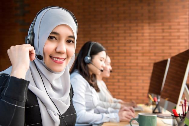 Femme musulmane travaillant dans un centre d'appels