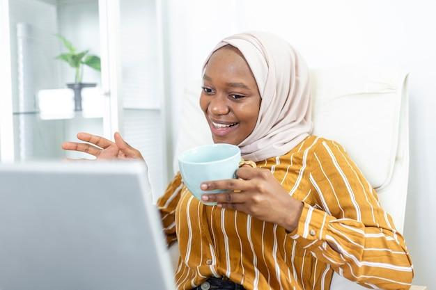 Femme musulmane travaillant avec ordinateur. jeune femme d'affaires arabe assise à son bureau à la maison, travaillant sur un ordinateur portable et buvant du café ou du thé. femme musulmane travaillant dans une maison et utilisant un ordinateur.