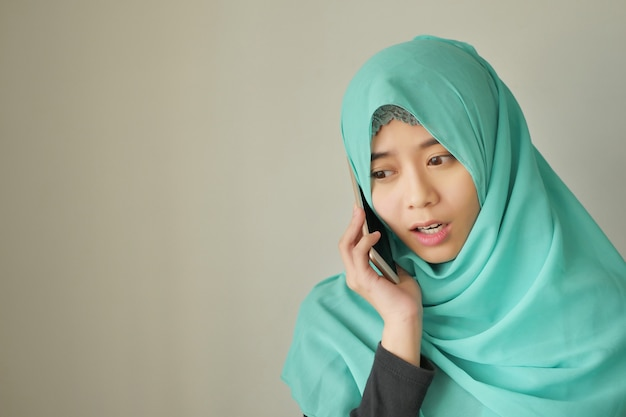 Femme musulmane triste, contrariée et frustrée avec un téléphone intelligent