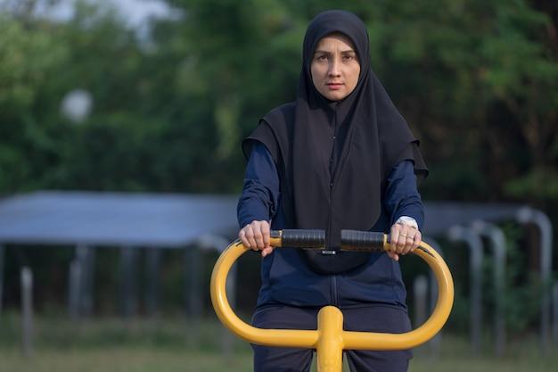 Femme musulmane vêtue de vêtements noirs et hijab couvre ses exercices de cheveux dans le parc.