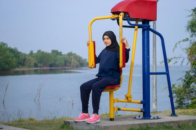 Une femme musulmane vêtue de vêtements noirs et de hijab couvre ses exercices avec les cheveux sur son poids.