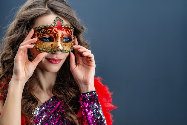 Femme mystérieuse portant un masque de carnaval sur fond bleu