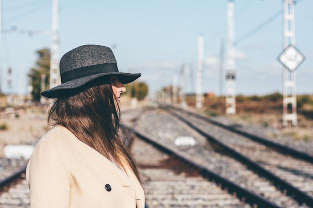 Femme mystérieuse en trench-coat beige et chapeau sur des voies ferrées abandonnées.