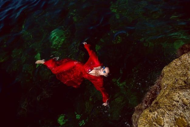 Femme nage dans la mer dans une robe longue rouge avec des lunettes de soleil