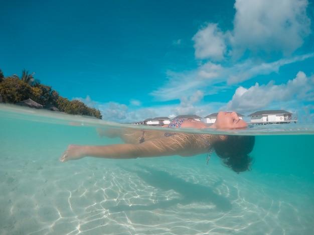 Femme nager et se détendre à la mer aux îles maldives
