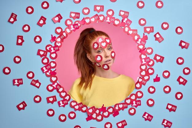 La femme narcissique aime l'attention sur internet. portrait de femme rousse parmi les boutons aime.