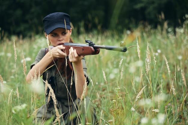 Femme sur la nature un abri avec une arme se penche sur la portée des feuilles vertes