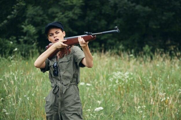 Femme sur la nature à la chasse avec une arme à feu en salopette verte feuilles vertes espace forestier