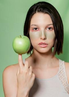 Femme naturelle équilibrant la pomme sur le doigt