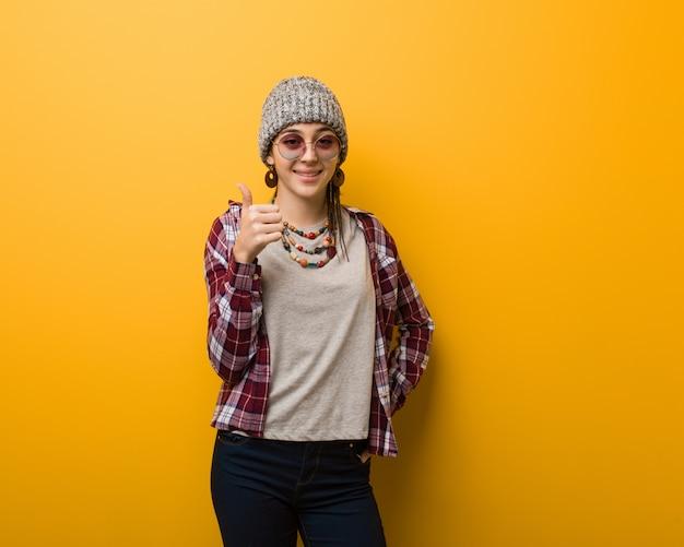 Femme naturelle jeune hippie souriante et levant le pouce vers le haut