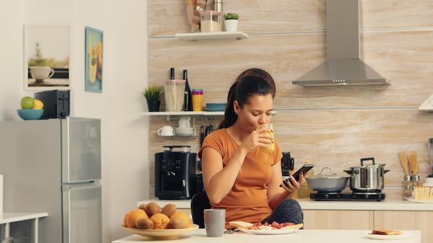 Femme naviguant au téléphone au petit-déjeuner et buvant du jus d'orange frais avec un repas bio sain et une tasse de café, en utilisant la technologie moderne seule dans la cuisine avant d'aller travailler.