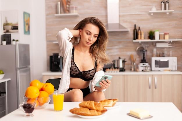 Femme naviguant sur smartphone portant de la lingerie sexy dans la cuisine à domicile pendant le petit déjeuner. femme séduisante avec des tatouages utilisant un smartphone portant des sous-vêtements temporaires le matin.