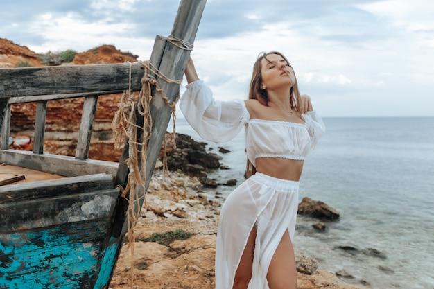Une femme à un navire cassé sur le rivage