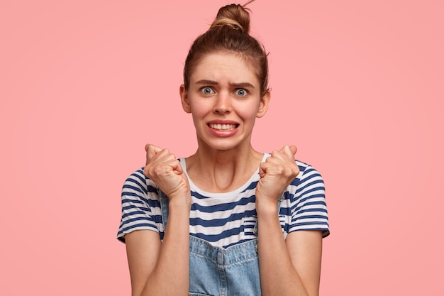 Une femme nerveuse mécontente garde les mains pressées dans les poings, serre les dents, a un regard désespéré