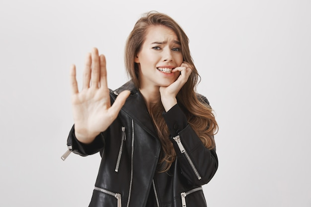 Femme nerveuse tend la main en arrêt, geste de refus, l'air effrayé