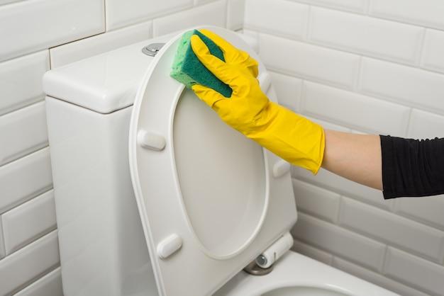 Femme nettoie dans la salle de bain. laver les toilettes