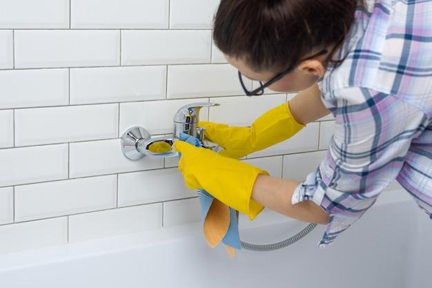 Femme nettoie dans la salle de bain à la maison