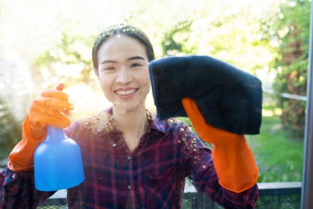 Femme nettoie la fenêtre, femme de ménage asiatique